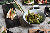 Bowl with edamame soy beans in pods served on wooden table with sushi rolls and boiled gyoza dumplings