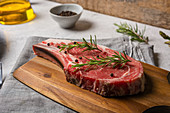 Uncooked t bone beef steak garnished with black pepper and rosemary sprigs