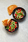 Tomato and bean salad with walnut naan bread served in pans