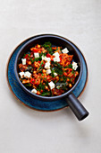 Greek orzo pasta with vegetables and dill in a pan