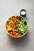 A baked potato and spinach bowl with spicy chickpeas and coriander