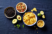 Ingredients for chilaquiles - black beans, tortilla chips, corn and salsa