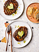 Grilled steaks topped with herb butter hearts