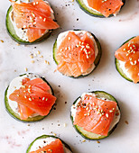 Sliced cucumber topped with salmon, cream cheese and sesame seeds