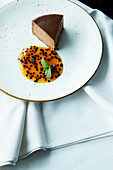 Truffle cake with sugared almonds and passion fruit sauce