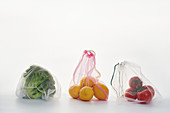 Food in net mesh bags on white background