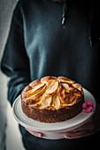 Hände halten Kuchenständer mit frisch gebackenem Apfelkuchen
