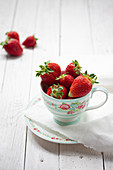 Fresh strawberries in porcelain cup