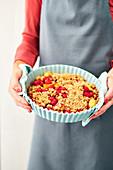 Frau hält Himbeer-Pfirsich-Crumble mit Haferstreuseln