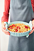 A woman holding a raspberry and peach crumble topped with oat crumbles