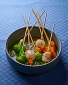 Fondue with scallops and vegetables on wooden skewers