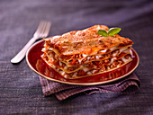 A piece of classic lasagne with a basil leaf