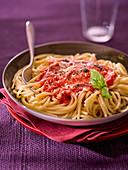 Spaghetti with tomato sauce and a basil leaf