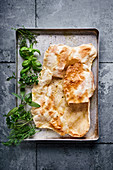 Baked tarte flambée dough with fresh herbs on a baking tray