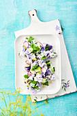 Purple potato salad with sour cream, cucumber and borage