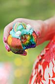 Frau hält angebissenen bunten Muffin mit Regenbogen-Deko