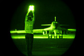Guiding B-1B Lancer bomber on taxiway at night