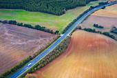 Road through farmland, aerial view