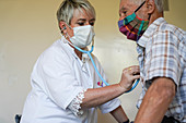 Man in consultation with a GP wearing a surgery mask