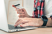 Shopping online with laptop and credit card