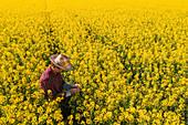 Oilseed rape farmer examining crop