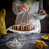 Lemon drizzle cake being glazed with icing