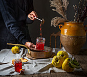 Quince jelly pouring into jam jars
