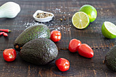 Avocado and lime with tomatoes , green onion and spices for mexican guacamole