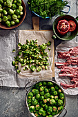 Cleaned Brussels sprouts in a colander, raw lamb chops and herbs