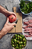 A pomegranate being sliced next to Brussels sprouts, lamb chops and herbs