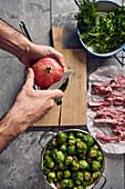 Granatapfel wird aufgeschnitten, daneben Rosenkohl, Lammkoteletts und Kräuter