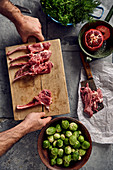 Lamb chops on a wooden board next to Brussels sprouts and herbs