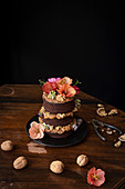 Chocolate naked cake with cream, walnuts and edible flowers