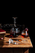 Glass of cognac with ice cubes and decanter
