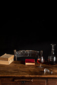 Glass of cognac, decanter and old books on wooden table