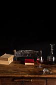 Holztisch mit Glas Cognac, Karaffe und alten Büchern