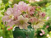 Rosafarbener Blumenstrauß aus Clematis und Sterndolde
