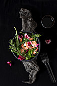 Salad with shrimps and green herbs garnished with eatible flowers