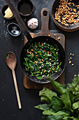 Catalan spinach with pine nuts in frying pan