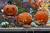 Halloween-Kürbisse mit Gesichtern und Blumendekor, Zierkürbisse, Maronen und Zweig mit Hagebutten