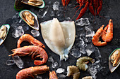 Assortment of various raw seafood - shrimps, kiwi mussels, squid and crawfish on ice