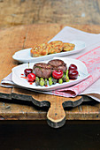 Venison medallions with glazed cherries and green asparagus