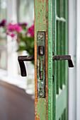 Alter Türbeschlag einer grünen Tür mit Patina