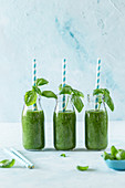 Three green smoothies in glass bottles with straws