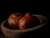 Two pomegranates in a wooden bowl