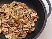 Stir-fried pork with mushrooms in a wok
