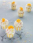 Käsesahne-Cupcakes mit Mandarine und bunten Zuckerstreuseln