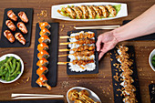Person with assorted sushi and asian food