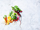 Assorted fresh vegetables and fruit on stone surface