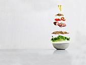 Salad ingredients floating over bowl